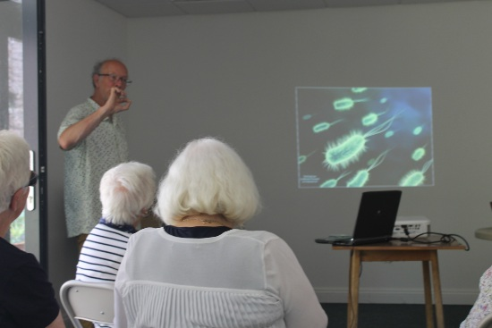 a man stands at the from of a room addressing an audience. He is showing an image of microscopic bacteria in the soil
