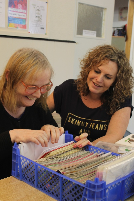 Two people looking through a variety of craft material
