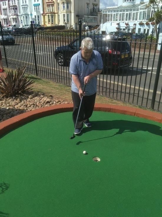 putting the golf ball into the hole on a crazy golf course