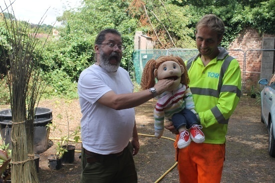 a man in a yellow top is holding a puppet of a young girl, which as the fingers of a man with a beard in her mouth. The man with a beard looks shocked