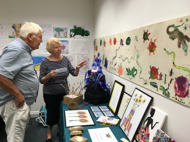 a man and a woman inspect a whole range of art work