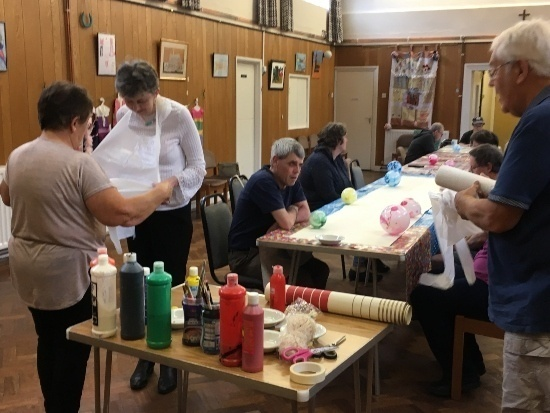 a room full of people preparing to paint, sitting at a long table, putting on bibs plus a table a paints