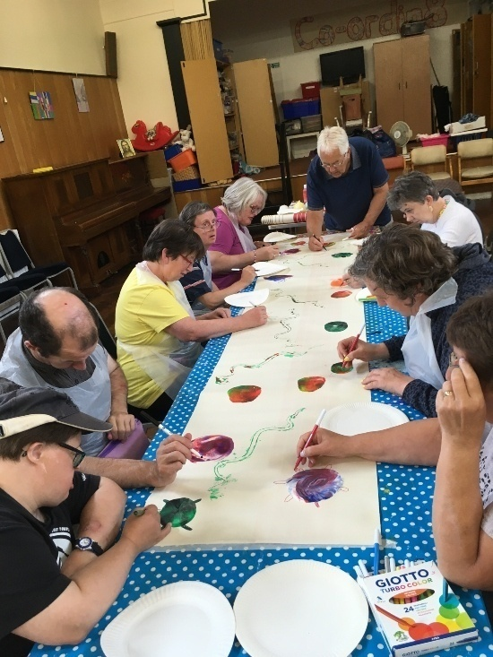 people on either side of a long table are on drawing and painting on a long canvass