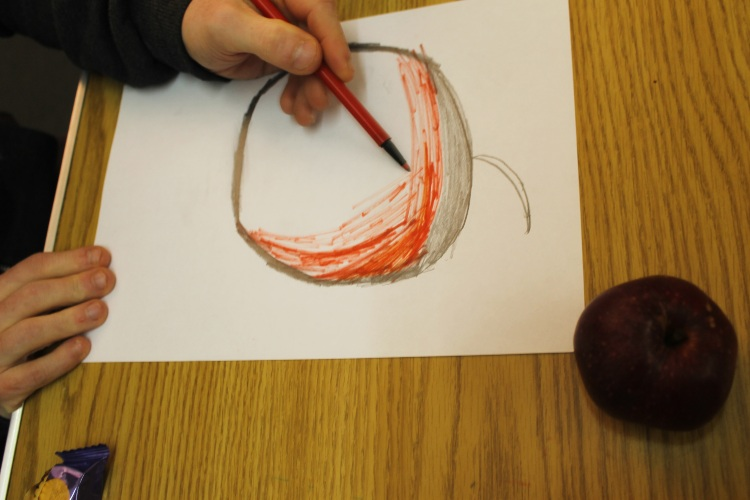 a red apple on a table with a person drawing them in colours