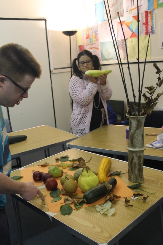 a man is arrange apples, courgets pears and other autumn fruit and veg on a table with autumn flowers. In the background a woman is holding a vegetable