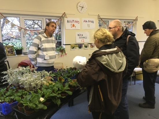 a man behind a table of plants. He is talking to two other people with another looking on