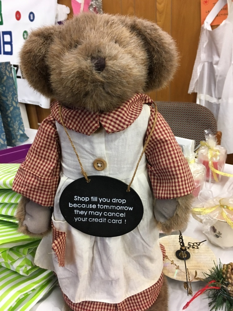 a teddy bear with a gingham shirt and smock wearing a sign that says: Shop till you drop because tomorrow they will cancel your credit card!