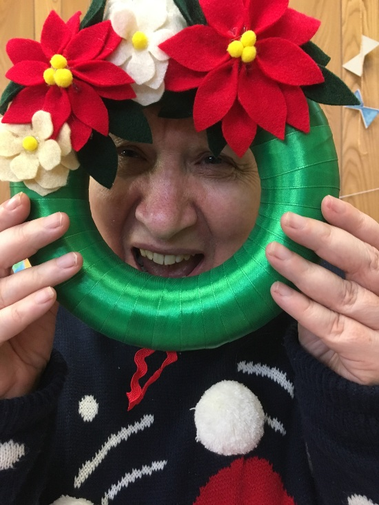 a person behind a seasonal wreath
