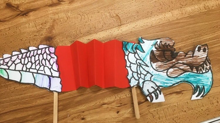 a chinese dragon made of paper with a red crepe paper middle and sticks at the bottom
