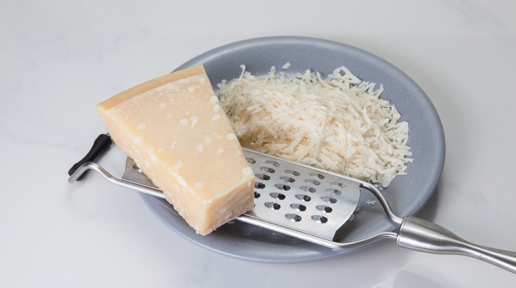 a piece of parmesan cheese next to a grater with grated cheese on a plate