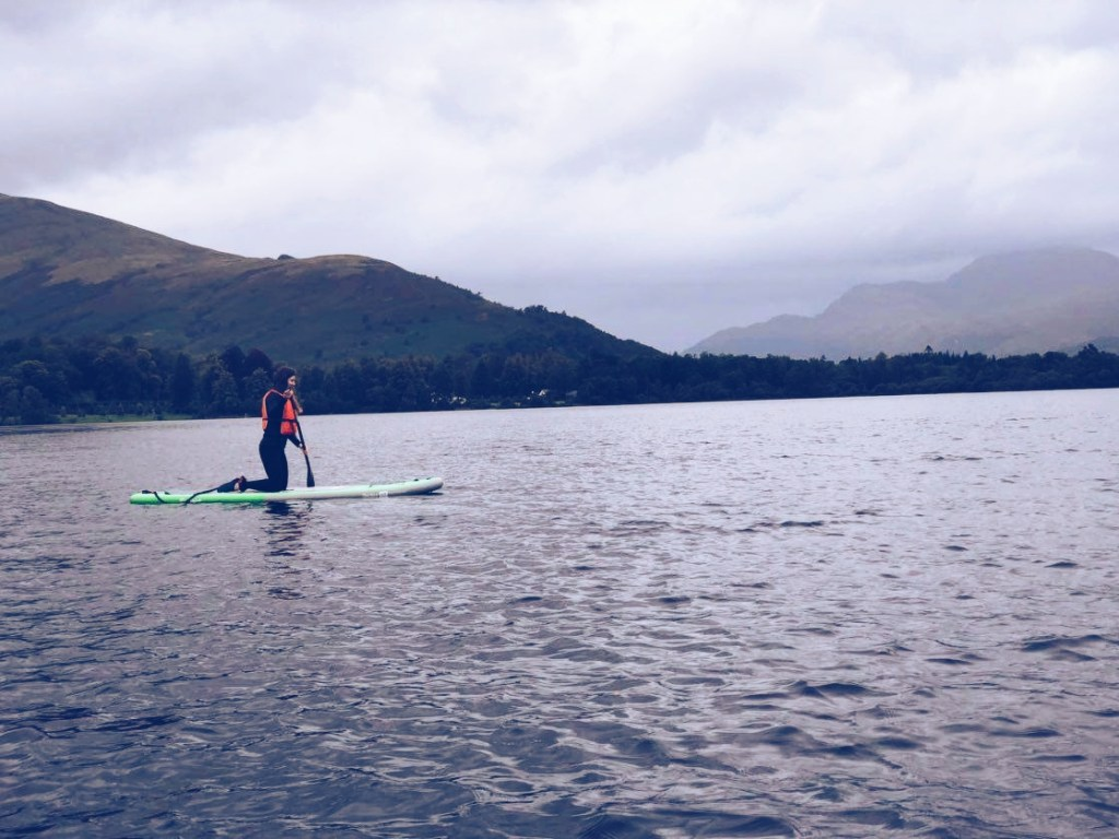 Roslyn on a green paddleboard paddling on Loch Lomond.