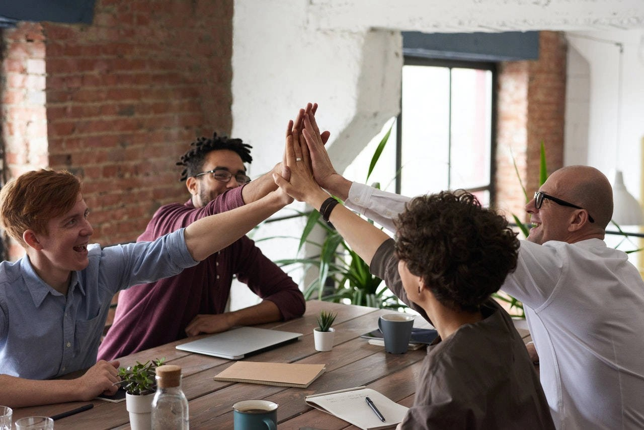 Photo of group high-five around a table.