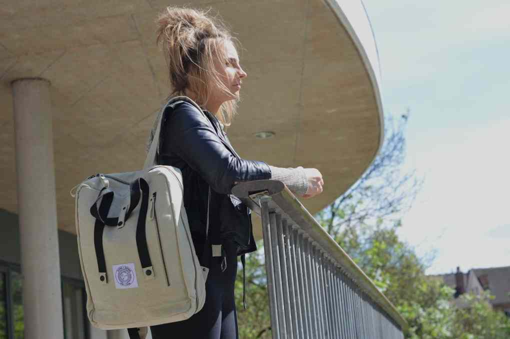 Nadia looks out over the Leamington park with her Poly Bag Vegan Backpack