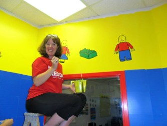 Maryann Gallagher paints colorful designs on the lego room walls.