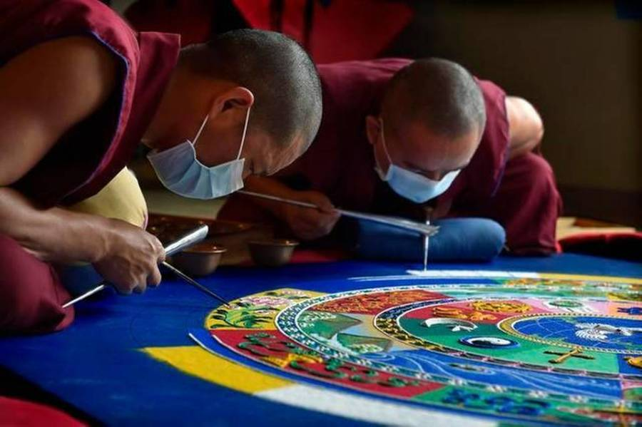 Tibetan monks from the Drepung Gomang Monastery in India building a sand mandala.