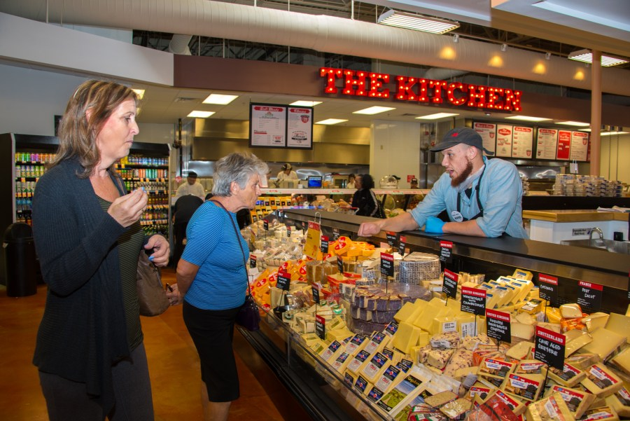 Customers tasting fresh cheese samples at the new Lucky's Market.