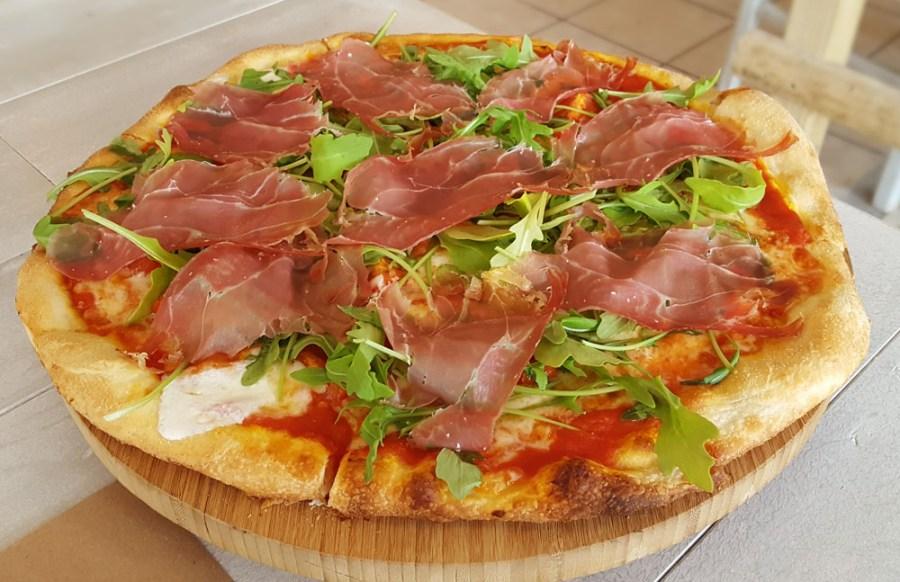 Italiana pizza at Il Faro topped with tomato sauce, Parma ham, cherry tomatoes, arugula and buffalo mozzarella.