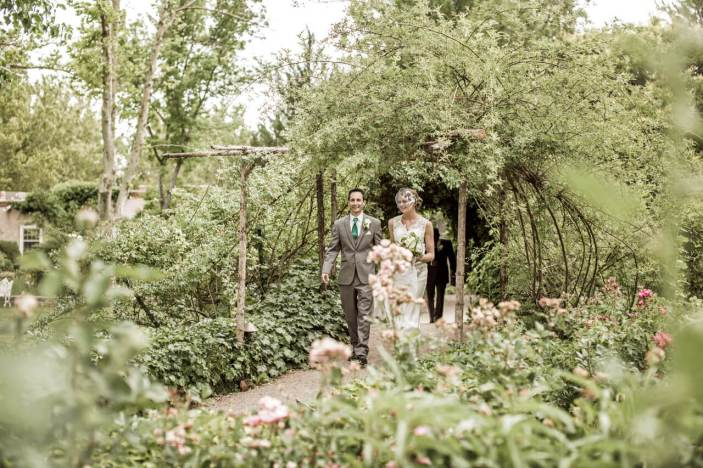 Bride and Groom Exit the Ceremony Through a Beautiful Garden