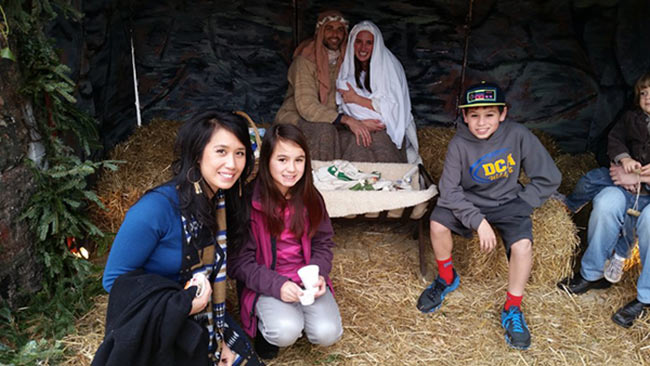Kay and kids in front of nativity