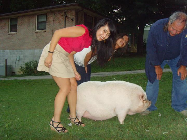 Kay standing next to a pig