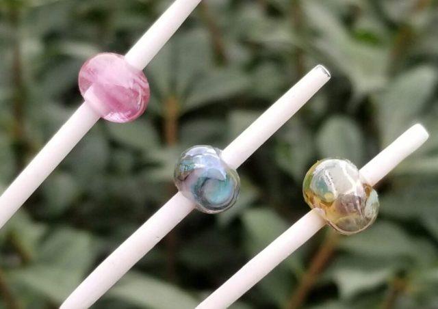 three glass beads on steel mandrels