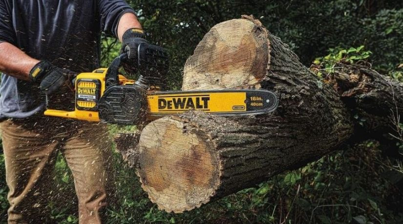 an image of a man using the best cordless chainsaw to cut a log of wood