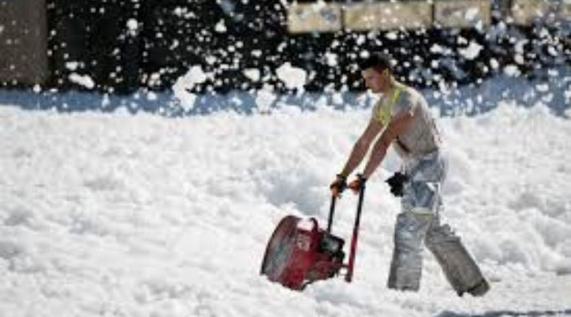 A man using the best cordless snow shovel to clear snow in the walkway