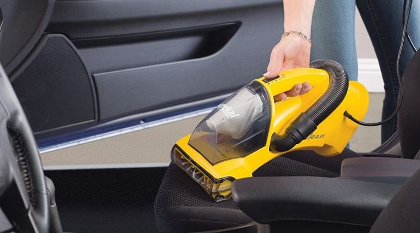 A person using a best cordless car vacuum (Eureka Easy Clean) to remove dirt in the car seats.