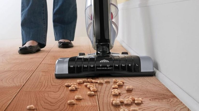 An example of the best cordless stick vacuum in use to remove debris and dust from the floor carpet