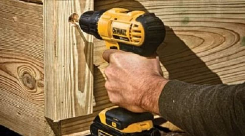 A woodworker using Dewalt model, an example of the best cordless drill under $150 to drill through a wood material