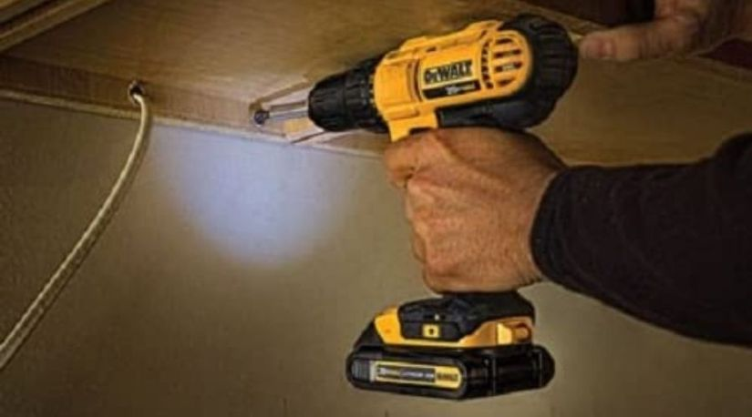 An image of a man using DEWALT 20V MAX Cordless Drill, one of the best 20v cordless drill to drill through the ceiling wall