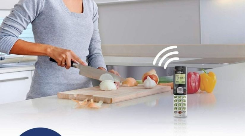 A video showing woman working on her kitchen and using one of the best cordless phones with powerful speakers for communication.
