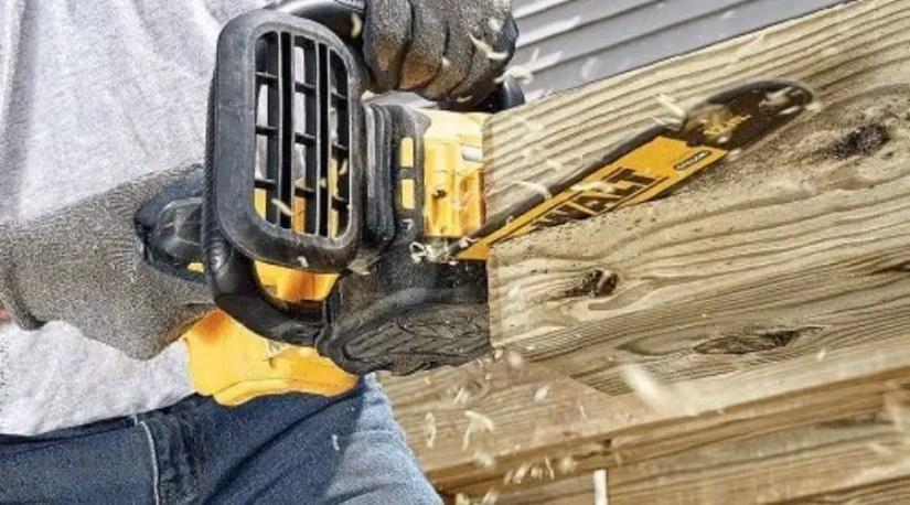 A man using DEWALT 20V MAX XR Chainsaw, one of the best chainsaw under $200 model to cut through a log of wood