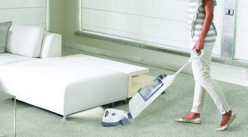 A lady using Shark Navigator Freestyle Upright Stick Cordless Bagless Vacuum for Carpet, one of the best cordless vacuum cleaners to remove dirt in her carpet