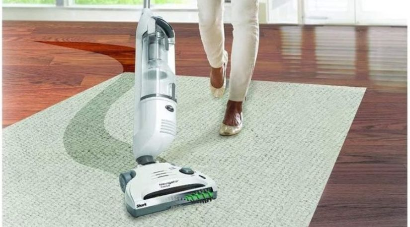 A lady cleaning a carpet using Shark Navigator Freestyle Upright Stick Cordless Bagless Vacuum for Carpet, another vital model among the best cordless vacuum cleaners