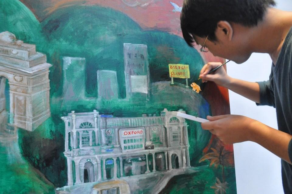 Shohei Emura painting a canvas of Delhi