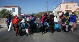 Asylum seekers carry their belongings, Lesbos, Greece, September 11 2020. Orestis Panagiotou/EPA-EFE