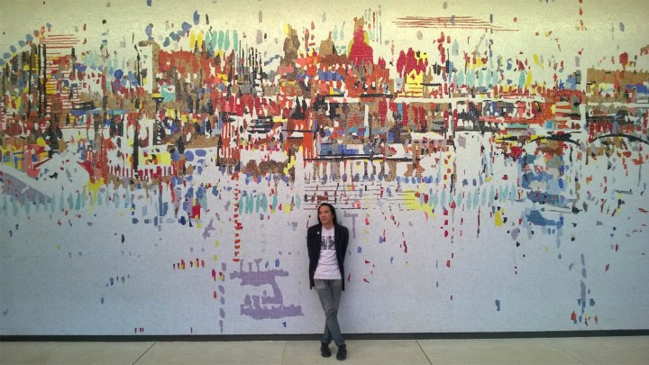 Corey Oada standing in front of Wayne Thiebaud's Water City mural