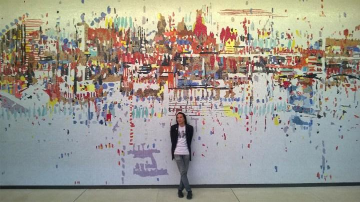 Corey Oada standing in front of Wayne Thiebaud's Water City mural