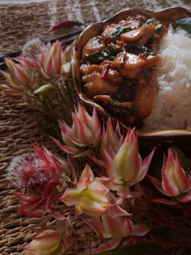 Tropical flowers around a bowl of Thai basil chicken.