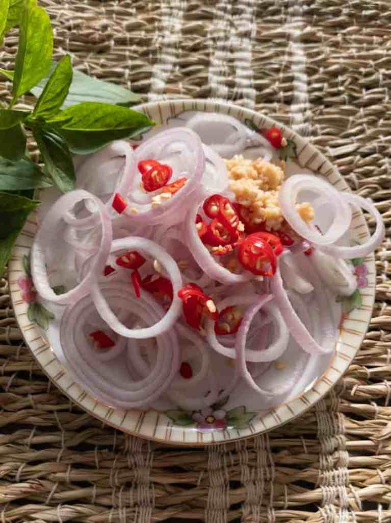 Sliced shallots, chilis, and minced garlic on a plate.