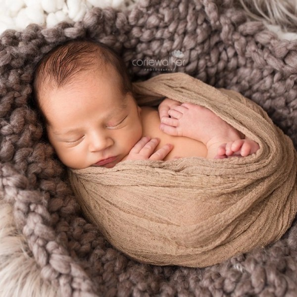 newborn boy wrapped in basket