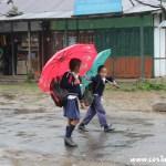 School children farewells in the rain, Yuksom, Sikkim, India
