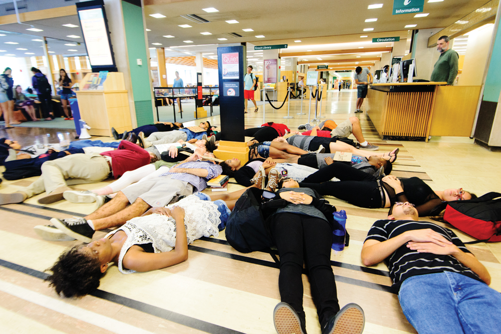 Students lie in the lobby of Olin Library to draw attention to the one-year anniversary of the disappearance of 43 Mexican students. (DAVID NAVADEH / sun CONTRIBUTOR)