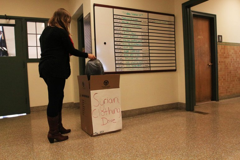A student donates clothing at a collection box for the Arab Student Association's winter clothing drive. (Dana Daniels / Sun Staff Photographer)