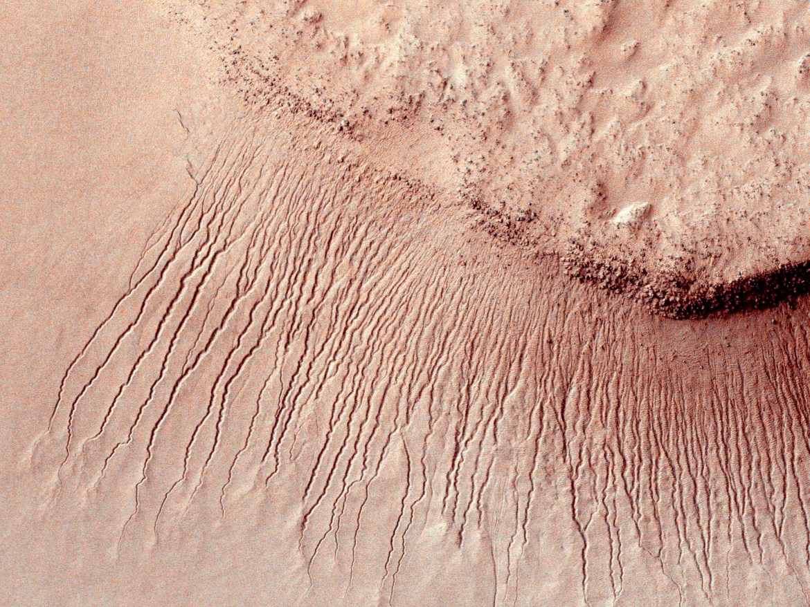 In an undated handout photo, portions of the Martian surface shot by NASA's Mars Reconnaissance Orbiter show many channels on a scarp in the Hellas impact basin. Scientists reported on Monday definitive signs of liquid water on the surface of present-day Mars, a finding that will fuel speculation that life, if it ever arose there, could persist to now. (Jet Propulsion Laboratory/University of Arizona/NASA) -- NO SALES; FOR EDITORIAL USE ONLY WITH STORY SLUGGED MARS WATER BY KENNETH CHANG. ALL OTHER USE PROHIBITED. --