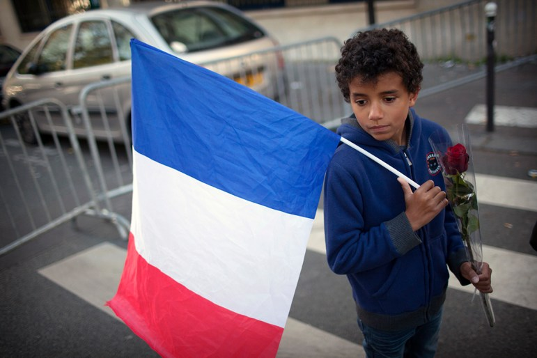 A young boy on Sunday with a French flag and a rose outside the Bataclan concert hall, where many were killed in Friday's terrorist attacks, in Paris, Sunday. (Pierre Terdjman / The New York Times)