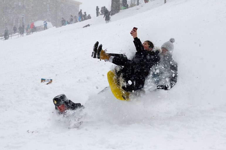 Students crash toward the bottom of Libe Slope as they sled down the hill on Tuesday.