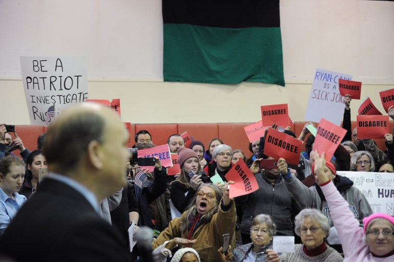 The Southside Community Center was filled with posters and a chanting crowd criticizing the Republican congressman at his town hall meeting.