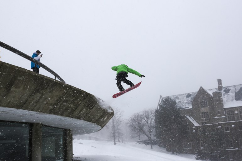 Mike Buldo Licciardi '17 jumps over a Uris Hall window on a snowboard during the snow day on Tuesday. (Katie Sims/Sun Staff Photographer)